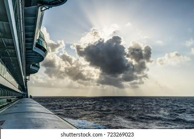Breakthrough sunshine on ocean horizon from side of cruise ship