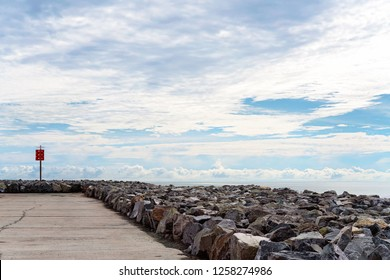 Breakwater built with large rocks jutting out over the ocean with a road for tourists and sightseers