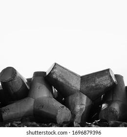 Breakwater concrete tetrapods, wave protection. Coastline, blue sky. Black and white photo. - Shutterstock ID 1696879396