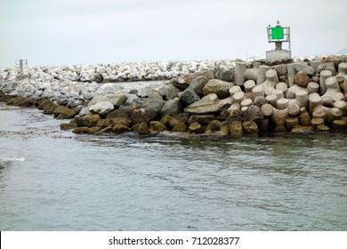 Breakwater made of boulders, granite rocks and round concrete blocks along entrance banks to Ventura harbor, port of San Buenaventura, Southern California
