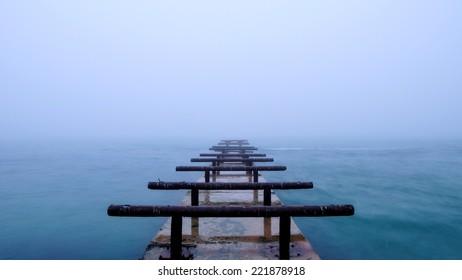 Breakwater on the misty sea