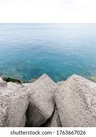Breakwater. Rocks by the blue sea merge with the horizon. Close-up of a rock-armor breakwater. Calm sea landscape. - Shutterstock ID 1763667026