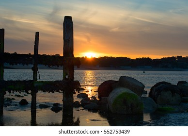 Breakwater and sea defence rocks in silhouette at Bembridge Harbour on the Isle of Wight during sunset.