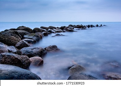 Breakwater Stones in the ocean dark mood for postcards about grief mourning or peaceful and soothing meditation and relaxation