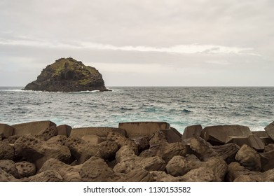Breakwater wall with a small island at a mausade temp on the coast of the city of Garachico north of Tenerife