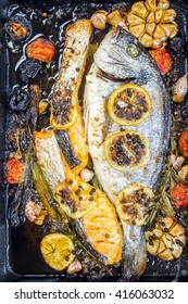 bream or dorade fish and salmon in a black pan with vegetables and spices