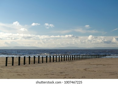 Brean beach wave break weathered posts providing a leading line into the sea. Bristol channel. Peaceful coastal concept