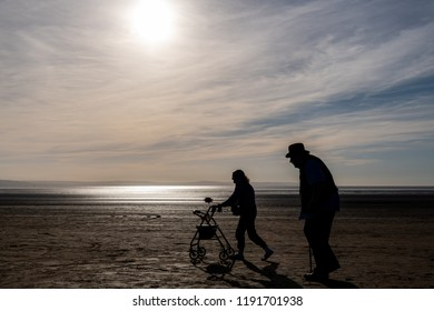 Brean, England, UK:  September 29, 2018: Older couple walking on the Brean Sands Beach in the late autumn afternoon
