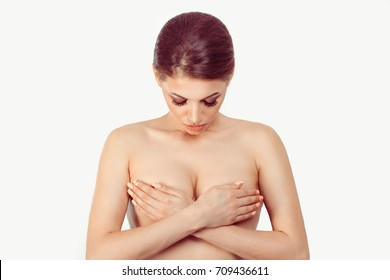 Breast Cancer Awareness, middle age female examining her breast for signs cancer by hands looking down thinking of mammal plastic cosmetic surgery isolated on white grey background wall