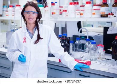 Breast cancer awareness ribbon against portrait of a smiling chemist leaning against desk
