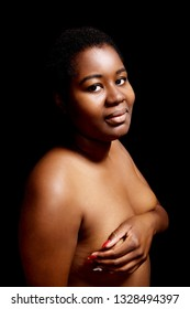 Breast cancer concept. African woman standing naked with covered breast.