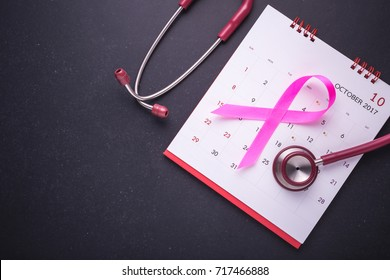 Breast Cancer concept : Pink ribbon symbol of breast cancer, calendar and doctor Stethoscope on black stone board background