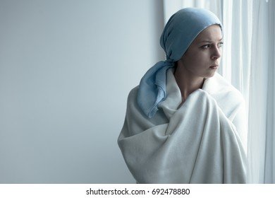 Breast cancer survivor covering herself in white blanket, and looking out the window