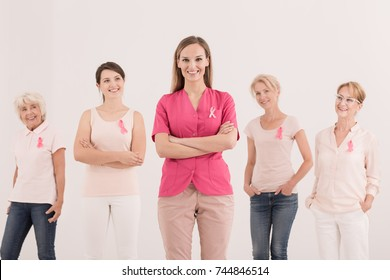Breast health educational concept, five women wearing pink ribbons as a symbol of cancer awareness and anti-cancer unity