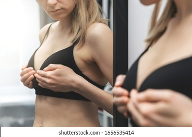 breast health - woman checking her breasts shape in front of the mirror at home