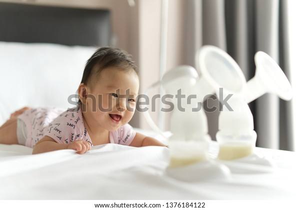 Breast milk in milk pump's bottles on the bed with selective focus on smiling crawling baby. The milk got from milk pump's machine and ready for the baby. Baby health care concept.
