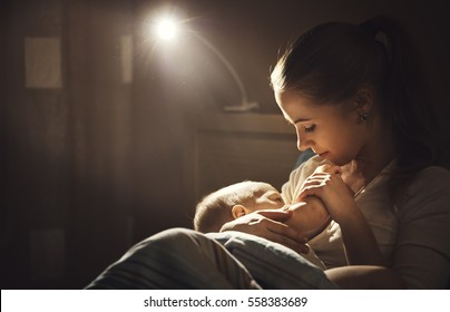 breast-feeding. mother breastfeeds the baby in the dark in bed