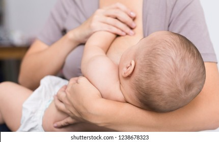 Breastfeeding. Newborn baby eating mothers breast milk, holding mom hand, closeup