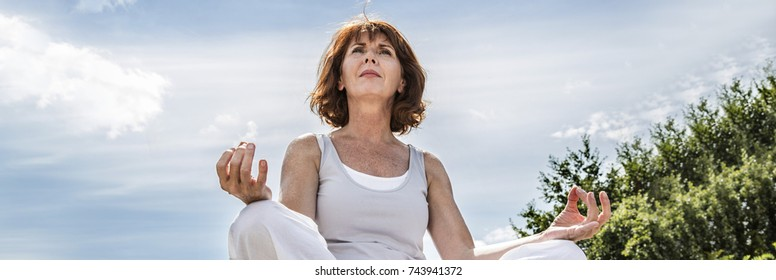 breathing outdoors - beautiful 50s woman sitting on a stone in yoga lotus position, seeking for spirituality over summer blue sky,low angle view, long banner