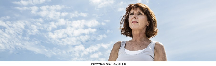 breathing outdoors - beautiful middle aged woman sitting on a stone in yoga lotus position, wearing white, seeking for balance over summer blue sky,low angle view, long banner