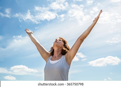 breathing outside - zen middle aged yoga woman looking up and raising her arms up,practicing meditation for freedom over summer blue sky,low angle view