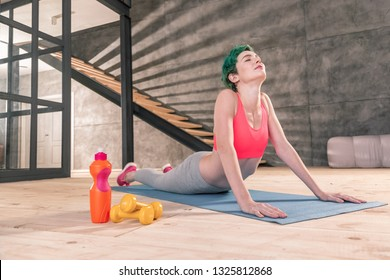 Breathing slowly. Slim green-haired woman breathing slowly while enjoying yoga in the morning