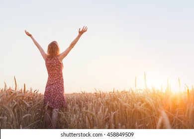 breathing, woman with raised hands enjoying sun in the field
