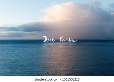 Breathless view of ocean and clouds. Just breath quote on the water with reflection