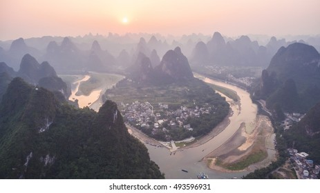 Breathtaking aerial view over beautiful karst mountain landscape and Li River covered with haze or fog at sunset in Yangshuo County, China