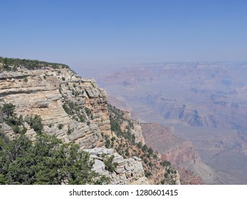 Breathtaking cliff with a view deck overlooking the beautiful land formations of Grand Canyon National Park on a hazy day from wildfire smoke.