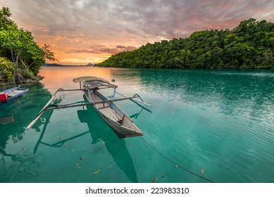 Breathtaking colorful sunset and traditional boat floating on blue lagoon in the Togean (or Togian) Islands, Central Sulawesi, Indonesia.