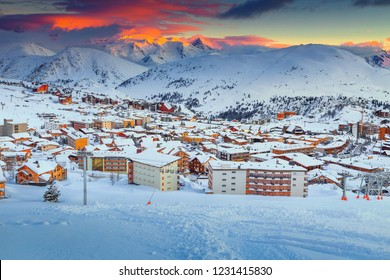 Breathtaking colorful winter sunset landscape, famous ski resort with modern, wooden buildings in French Alps, Alpe D Huez, France, Europe