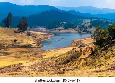 Breathtaking landscape vista of Mannavanur lake with surrounding mountains near Kodaikanal.