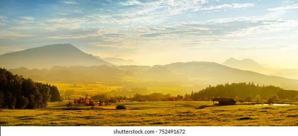 Breathtaking lansdcape of Austrian countryside on sunset. Dramatic sky over idyllic green fields of Anstrian Central Alps on early autumn evening.