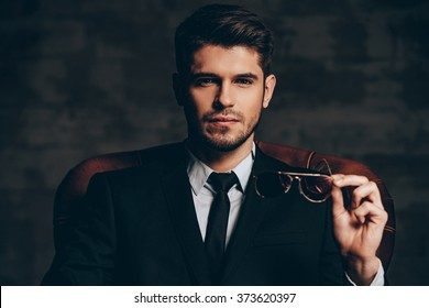 Breathtaking look.Portrait of young handsome man in suit holding his sunglasses and looking at camera while sitting in leather chair against dark grey background