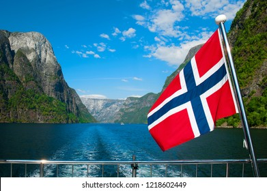 The Breathtaking Norwegian Aurlandsfjord and Naeroyfjord - UNESCO protected fjord - cruise (Flam- Gudvangen) on Norway in a Nutshell Tour. One of the narrowest fjords in Europe Naeroyfjord and a flag.