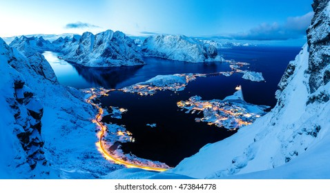 Breathtaking panorama of night and sleepy town surrounded by snowy peaks, Reinebringen, Lofoten, Norway