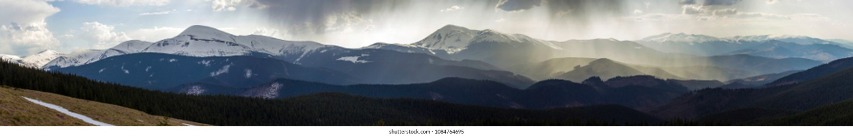Breathtaking panoramic view of magnificent foggy Carpathian mountains, covered with ever-green forest on misty quiet morning or evening under dark cloudy sky. Mountains snow covered tops in distance.