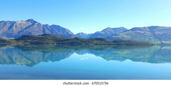 A breathtaking panoramic view of a random lake in NZ while driving. Incredible visual image featuring the mountainous range and its reflection upon the surface of the lake.