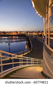 Breathtaking picture along pier back to seafront town alight with glow of evening lights in town