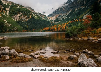 Breathtaking Popradske pleso mountain lake with its reflections Autumn forest, High Tatras in the background