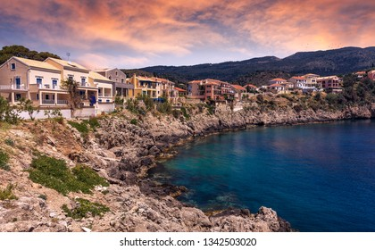 Breathtaking rocky coastline with colorful houses of Assos village, Kefalonia Island. Greece, impressively beautiful seascape with picturesque sky during sunset.
