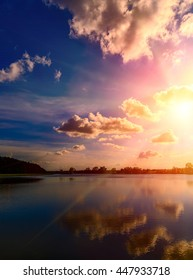 breathtaking scenery. dark-blue sky with clouds. reflection in water, for design . multicolored majestic sunset with a halo of sunlight. fantastic picturesque scene. use as background