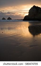 breathtaking seascape colorful portrait of sandy beach praia da rocha with huge rocks in sunset reflecting in water, algarve, south portugal