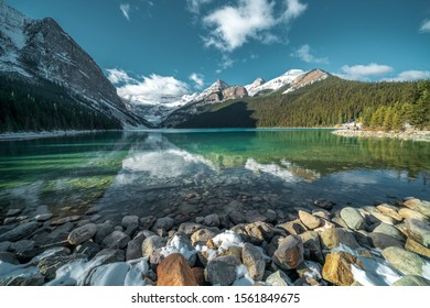 A breathtaking shot of beautiful stones under the turquoise water of a lake and hills in the background