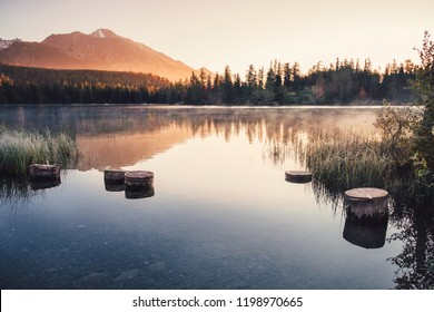 Breathtaking Strbske mountain lake with its reflections on sunrise in Autumn, High Tatras in the background