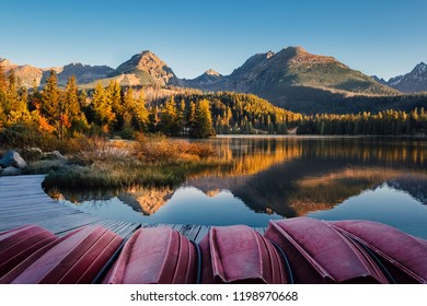 Breathtaking Strbske pleso lake with boat on foreground and High Tatras mountain reflections at sunsise in Autumn