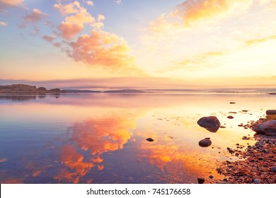 Breathtaking sunrise seascape scenery over Northern sea in Sweden. Epic dawn sea landscape. Lilac and red yellow colors scene. X letter guessed in shape form factor of cloud.