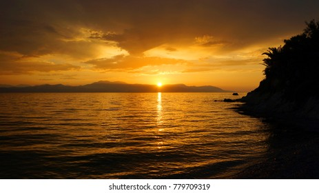 Breathtaking sunset with golden colors, scattered clouds and calm sea
