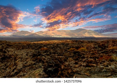 A breathtaking sunset and setting sun behind volcanic mountains. Volcanic, desert landscape. Beautiful warm orange sky. Photo taken in Lanzarote, Canary Islands, Spain